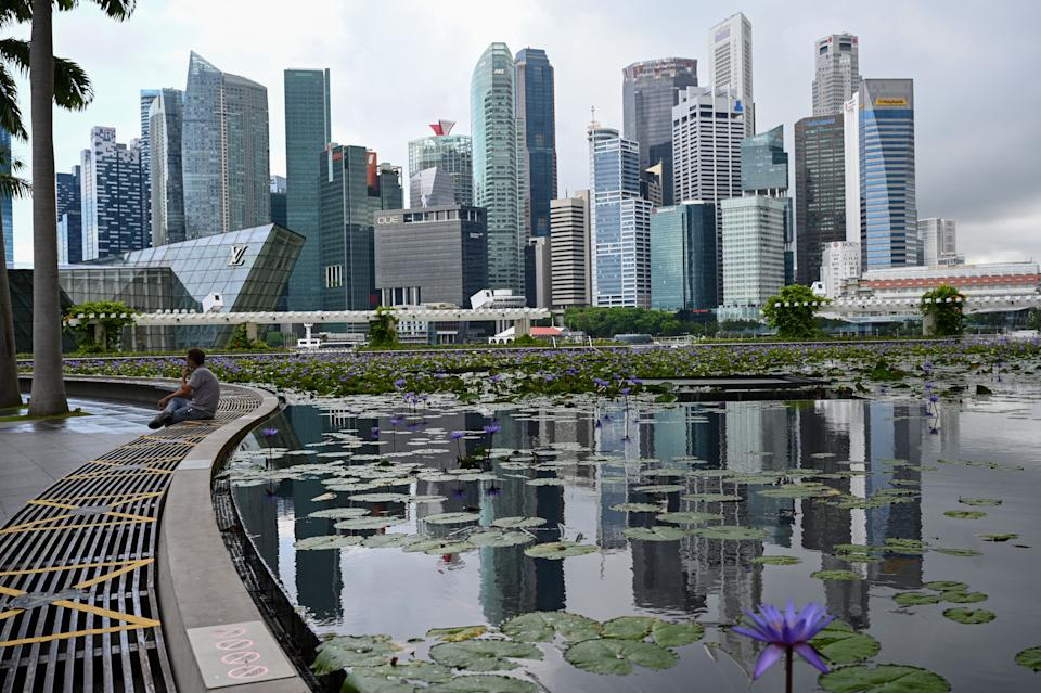 A man sits next the pond at Marina Bay Sands in Singapore on May 14, 2021, ahead of tightening restrictions over concerns of a rise in Covid-19 coronavirus cases. (Photo by Roslan Rahman / AFP) (Photo by ROSLAN RAHMAN/AFP via Getty Images)