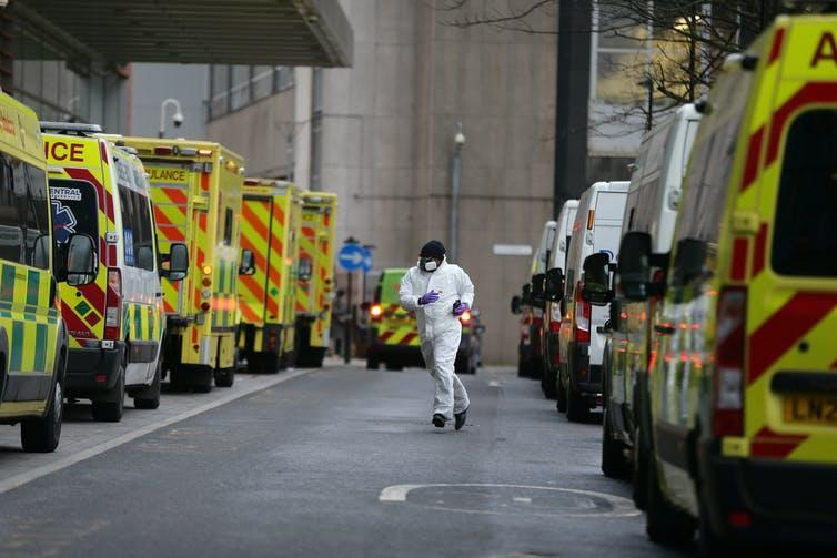 A health worker runs between two rows of ambulances.