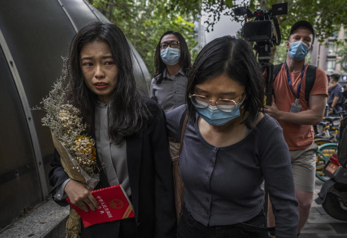 Leading figure in China's #MeToo movement Zhou Xiaoxuan, left, is comforted after being accosted by unknown people while speaking to journalists and supporters outside the Haidian District People's Court before a hearing in her case against prominent television host Zhu Jun on September 14, 2021 in Beijing, China. / Credit: Kevin Frayer/Getty
