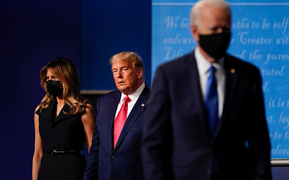 First lady Melania Trump, left, and President Donald Trump, center, remain on stage as Democratic presidential candidate former Vice President Joe Biden, right, walk away at the conclusion of the second and final presidential debate Thursday, Oct. 22, 2020, at Belmont University in Nashville, Tenn. - AP