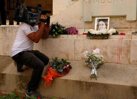 A news cameraman films an impromptu memorial on the Great Siege Monument during a protest by journalists following the assassination of investigative journalist Daphne Caruana Galizia in a car bomb attack three days ago, in Valletta, Malta, October 19, 2017.  REUTERS/Darrin Zammit Lupi
