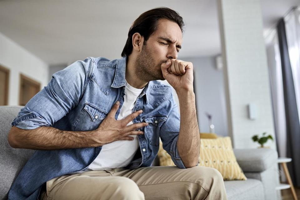Sick man holding his chest in pain while coughing in the living room.