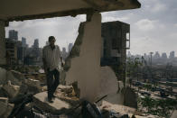 In this image released by World Press Photo, Thursday April 15, 2021, by Lorenzo Tugnoli, Contrasto, for The Washington Post, part of a series titled Port Explosion in Beirut, which won first prize in the Spot News Stories category, shows Abdullah Dalloul walks in the ruins of his former home on August 14, 2020, which was destroyed by the blast in the port of Beirut, Lebanon. Following the explosion, he and his family squatted in the damaged building with no water or electricity. (Lorenzo Tugnoli, Contrasto, for The Washington Post, World Press Photo via AP)