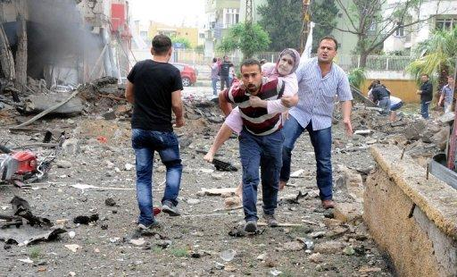 Residents evacuate a wounded woman to hospital after deadly explsions went off on May 11, 2013 in Reyhanli, Turkey