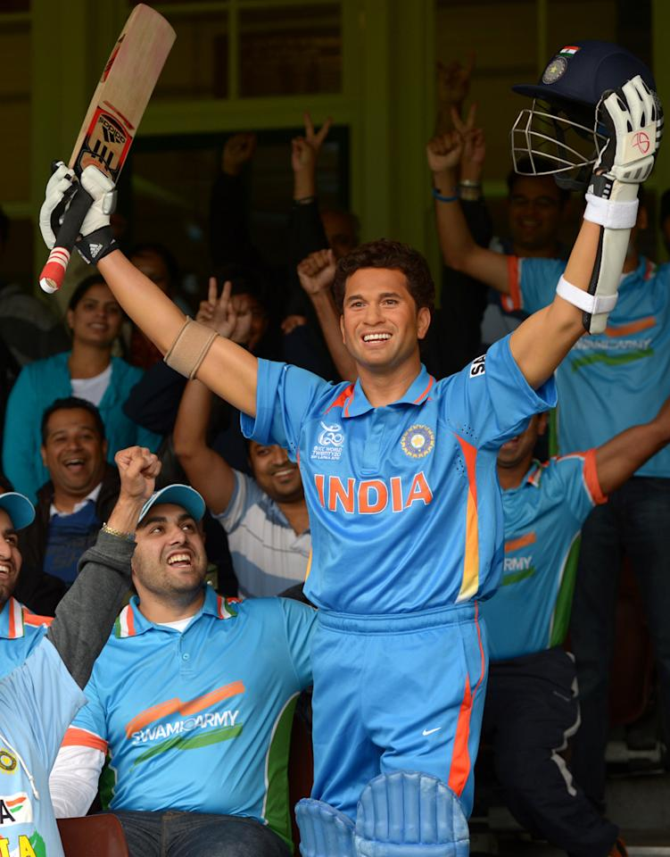 "A group of Indian cricket fans kmnown as the ""Swami Army"" shout slogans next to a wax figure of India's legendry cricket star Sachin Tendulkar, at the Sydney Cricket Ground in Sydney on April 20, 2013. The new wax figure of Tendular will be placed in the sports zone of Madame Tussauds in Sydney.                       AFP PHOTO / Saeed Khan        (Photo credit should read SAEED KHAN/AFP/Getty Images)"