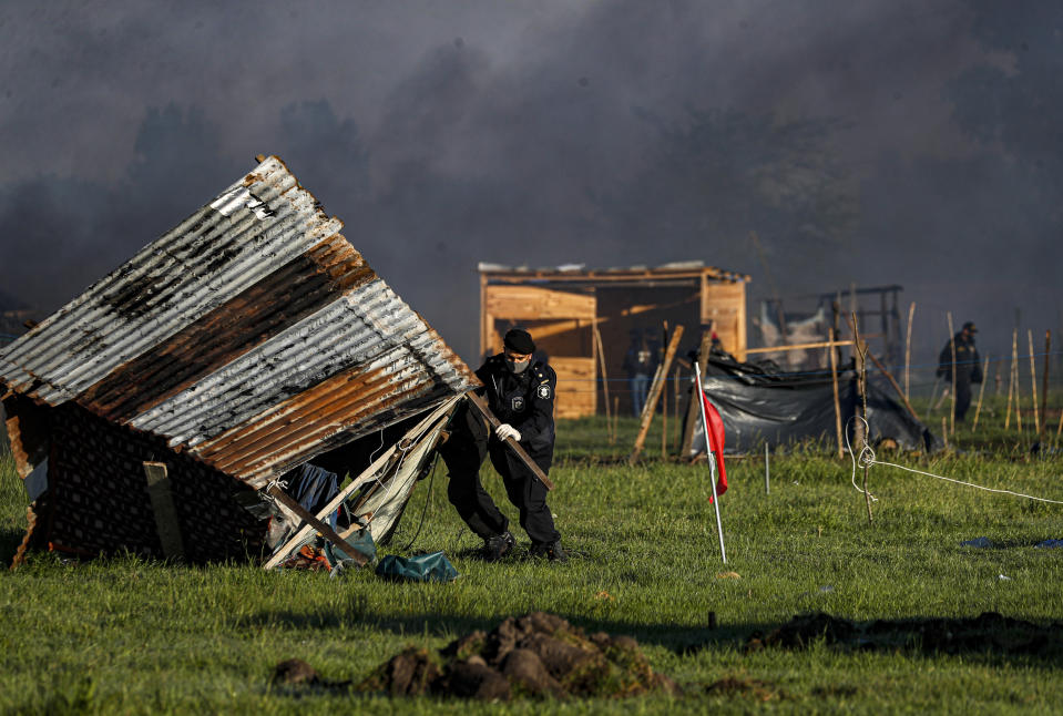Police destroy shack homes as they carry out evictions at a squatters camp in Guernica, Buenos Aires province, Argentina, Thursday, Oct. 29, 2020. A court ordered the eviction of families who are squatting here since July, but the families say they have nowhere to go amid the COVID-19 pandemic. (AP Photo/Natacha Pisarenko)