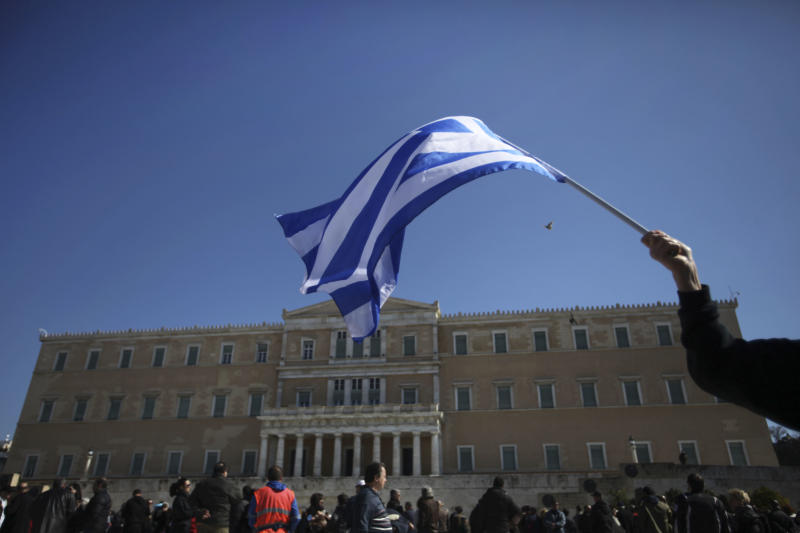 A protester waves a Greek flag in front of the parliament in central Athens as few hundred protesters gather to protest against the government's austerity measures during an anti-government rally on Sunday, Feb. 19, 2012.(AP Photo/Petros Giannakouris)