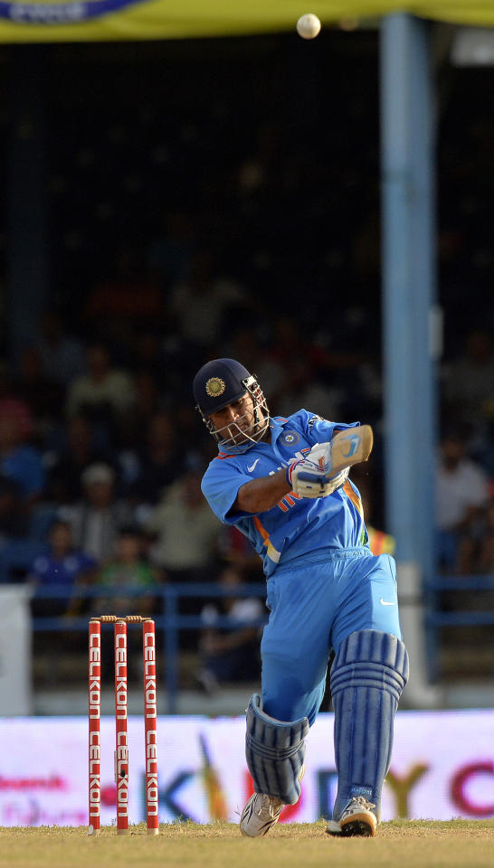 Indian cricket team captain Mahendra Singh Dhoni hits a boundary during the final match of the Tri-Nation series between India and Sri Lanka at the Queen's Park Oval stadium in Port of Spain on July 11, 2013. India defeated Sri Lanka by 1 wicket to win the series. AFP PHOTO/Jewel Samad
