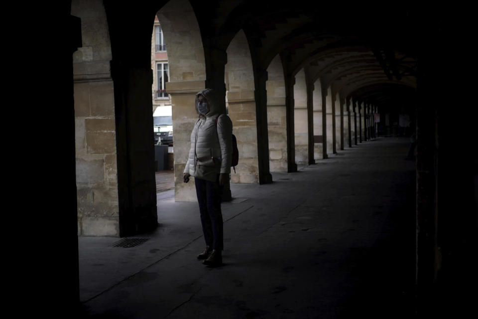 A woman wears a mask as she walks in a street of Paris, Tuesday, Oct. 27, 2020. France's government is holding emergency virus control meetings Tuesday and warning of possible new lockdowns, as hospitals fill up with new COVID patients and doctors plead for backup. (AP Photo/Thibault Camus)