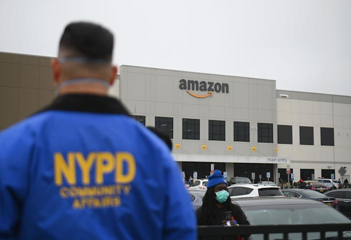 NYPD Community Affairs officer watches as Amazon workers at Amazon's Staten Island warehouse strike in demand that the facility be shut down and cleaned after one staffer tested positive for the coronavirus on March 30, 2020 in New York. - Amazon employees at a New York City warehouse walk off the job March 30, 2020, as a growing number of delivery and warehouse workers demand better pay and protections in the midst of the COVID-19 pandemic. (Photo by Angela Weiss / AFP) (Photo by ANGELA WEISS/AFP via Getty Images)