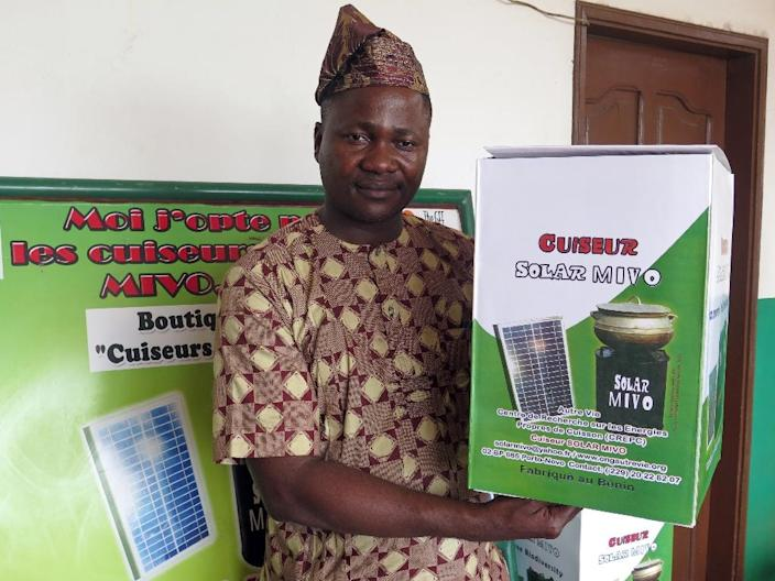 Executive director of the charity Autre Vie (Another Life) Romuald Djivoessoun poses with a solar-powered cooker in Porto-Novo (AFP Photo/)