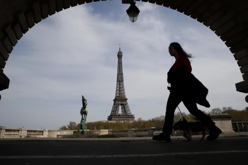 FILE - In this Tuesday, April 7, 2020 file photo, a woman walks her dog on a Paris bridge, with the Eiffel tower in background, during a nationwide confinement to counter the COVID-19. The European Union announced Tuesday, June 30, 2020 that it will reopen its borders to travelers from 14 countries, but most Americans have been refused entry for at least another two weeks due to soaring coronavirus infections in the U.S. (AP Photo/Christophe Ena, File)