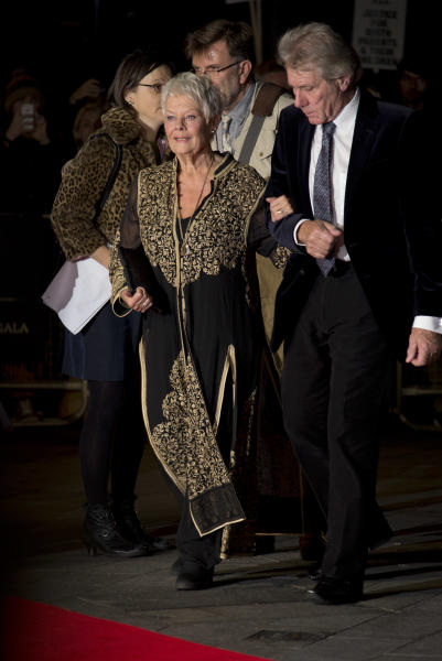 British actress Dame Judi Dench, left, arrives with David Mills on the red carpet for the screening of Philomena, as part of the 57th BFI London Film Festival, at a central London cinema, Wednesday, Oct. 16, 2013. (Photo by Joel Ryan/Invision/AP)