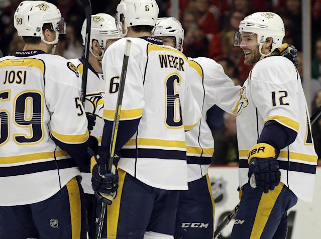 Nashville Predators' Mike Fisher (12), right, celebrates with teammates after scoring a goal during the first period of an NHL hockey game against the Chicago Blackhawks in Chicago, Friday, March 14, 2014. (AP Photo/Nam Y. Huh)