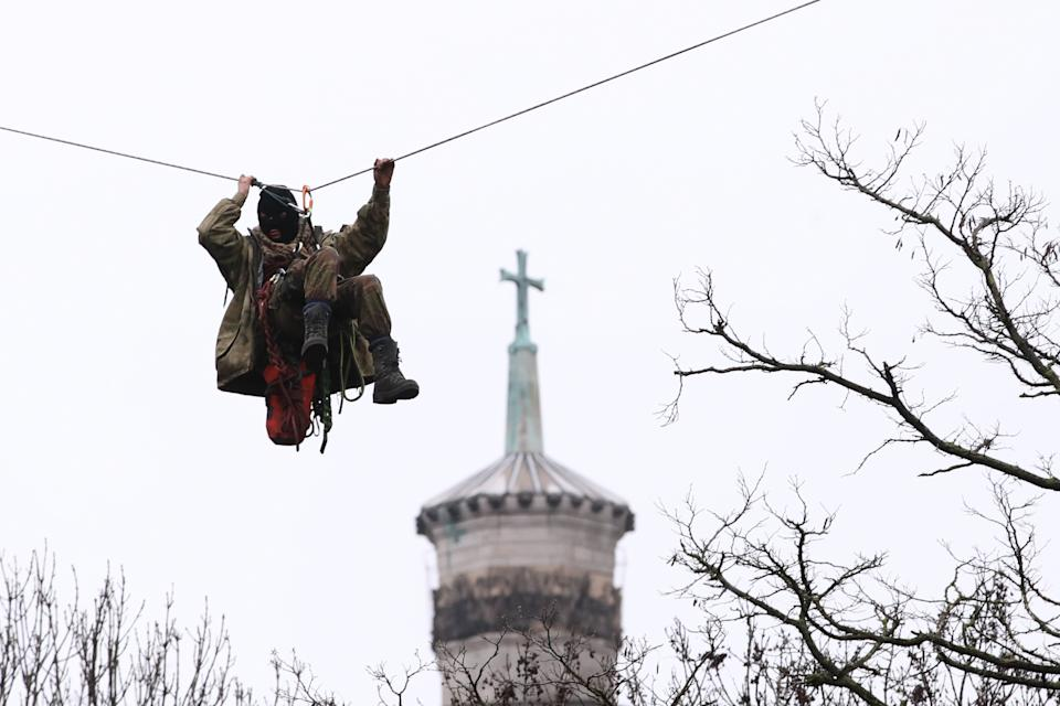 HS2 Rebellion protester on a zip line between two trees in an encampment in Euston Square Gardens in central London, where the protesters have built a 100ft tunnel network, which they are ready to occupy, after claiming the garden is at risk from the HS2 line development. The spire of St Pancras New Church is in the background. Picture date: Wednesday January 27, 2021.