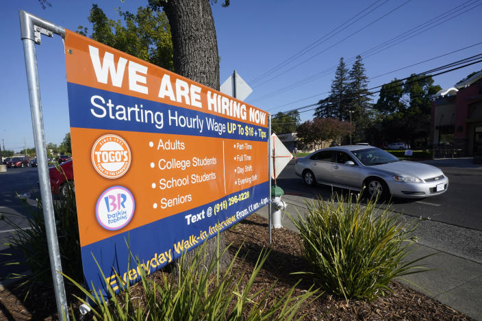 A car passes a hiring banner in Sacramento, Calif., Friday, July 16, 2021. Hiring in California slowed down in June 2021 as employers in the nation's most populous state tried to coax reluctant workers back into their pre pandemic jobs before the nation's expanded unemployment benefits expire in September. (AP Photo/Rich Pedroncelli)
