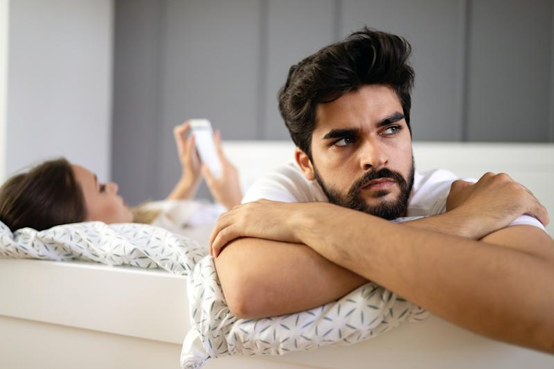Couple problems. Husband is frustrated upset and unsatisfied while his internet addict wife is using mobile phone in social network