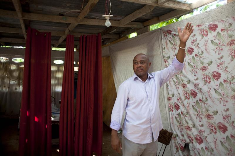 """Film Director Raoul Peck gives a tour on the set of his film """"Murder in Pacot,"""" a home that was damaged in the 2010 earthquake in Port-au-Prince, Haiti, Friday, April 11, 2014. Peck's movie focuses on a well-to-do family whose house is almost completely destroyed. """"Visually it was incredible — this image of wealth, totally crumbled,"""" said Peck, a former Haitian culture minister and now president of a prestigious French film school. (AP Photo/Dieu Nalio Chery)"""