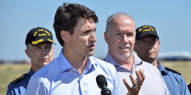 Prime Minister Justin Trudeau, accompanied by British Columbia's Premier John Horgan, addresses the media after touring areas affected by wildfires in Williams Lake, B.C. on July 31, 2017.