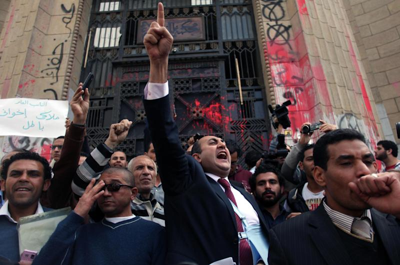 "FILE - In this Tuesday, March 26, 2013 file photo, Former presidential candidate Khaled Ali, center, chants slogans during a protest in front of the general prosecutor's office in Cairo, Egypt. Ali says he will not take part in upcoming presidential elections, calling them a ""farce."" (AP Photo/Khalil Hamra, File)"