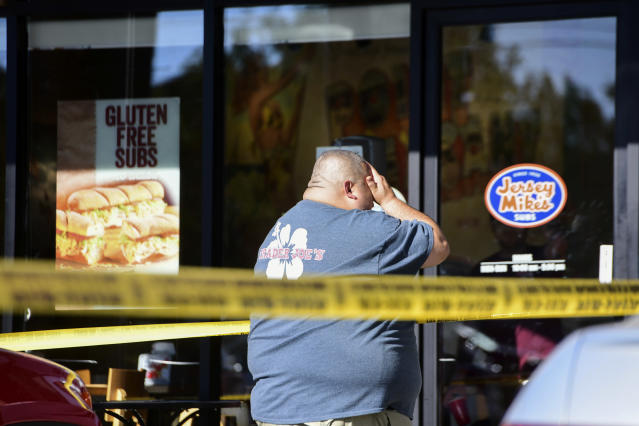 <p>A Trader Joe's employee is distraught as he recounts his experience just outside the store where a man held employees hostage and killed one woman in L.A. on Saturday. (Photo: Christian Monterosa via AP) </p>