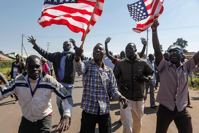 <p>Supporters of former US president Barack Obama wave US flags as they cheer to welcome Obama during an opening ceremony of the Sauti Kuu Sports, Vocational and Training Centre in his ancestral home Kogelo, some 400km west of the capital Nairobi, Kenya on July 16, 2018. (Photo: Dai Kurokawa/EPA-EFE/REX/Shutterstock) </p>