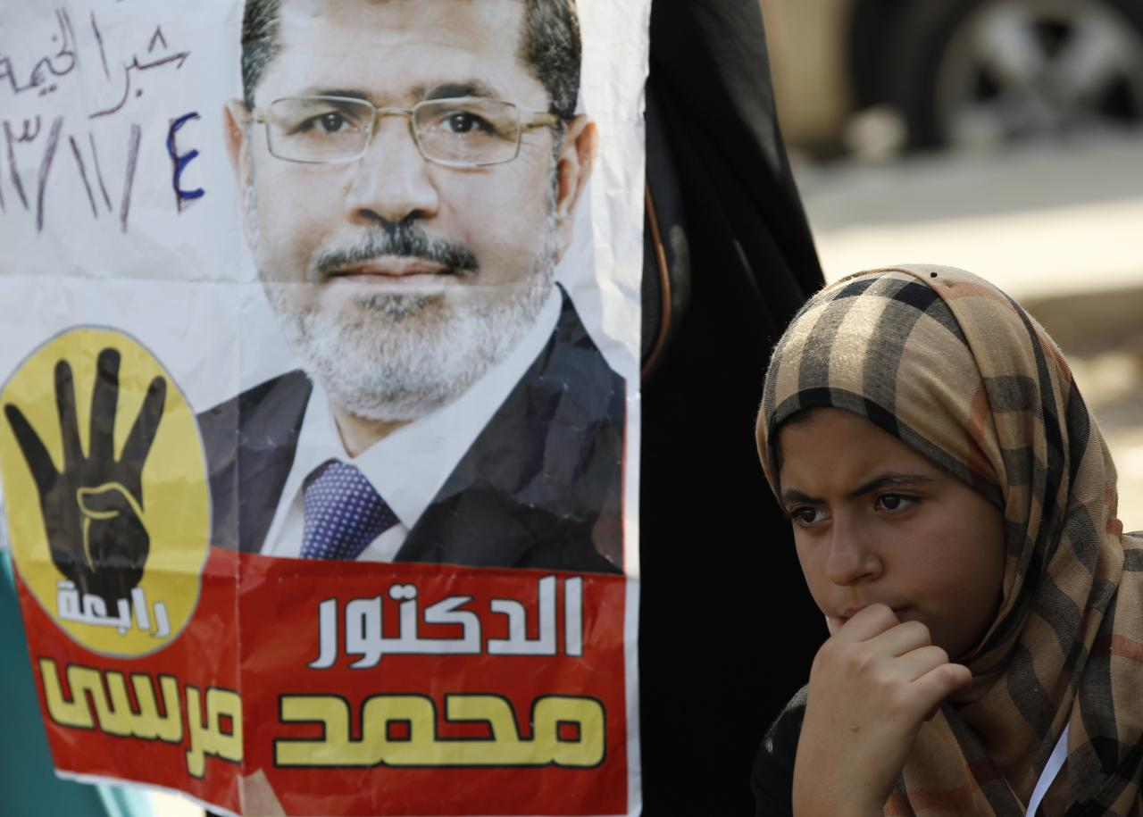 """A supporter of the Muslim Brotherhood and ousted Egyptian President Mohamed Mursi stands next to a poster of Mursi during a protest outside the police academy, where Mursi's trial took place, on the outskirts of Cairo, November 4, 2013. Mursi struck a defiant tone on the first day of his trial on Monday, chanting 'Down with military rule', and calling himself the country's only 'legitimate' president. Mursi, an Islamist who was toppled by the army in July after mass protests against him, appeared angry and interrupted the session repeatedly, prompting a judge to adjourn the case. The words on the poster read, """"Mursi is our president."""" REUTERS/Amr Abdallah Dalsh (EGYPT - Tags: POLITICS CIVIL UNREST)"""