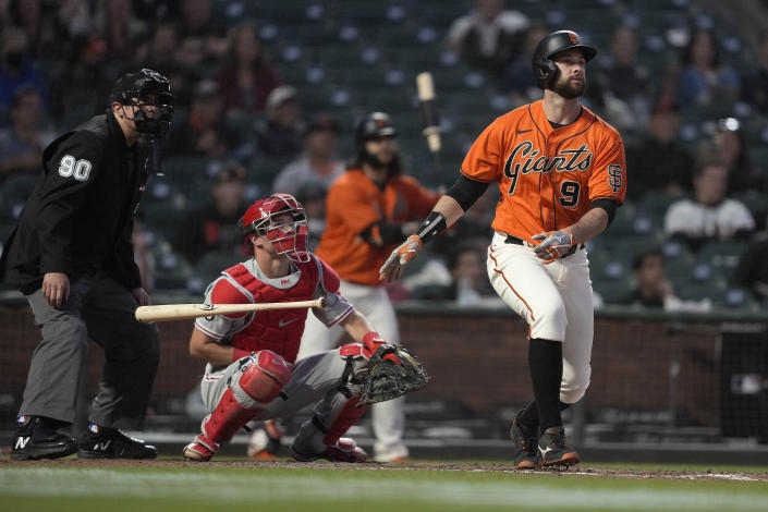 San Francisco Giants' Brandon Belt (9) watches his solo home run in front of Philadelphia Phillies catcher Andrew Knapp during the fifth inning of a baseball game Friday, June 18, 2021, in San Francisco. (AP Photo/Tony Avelar)