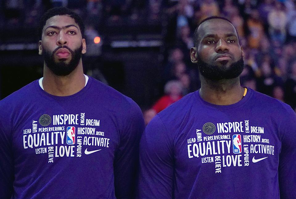 LeBron James #23 (R) and Anthony Davis #3 of the Los Angeles Lakers (L) stands for the National Anthem prior to the start of an NBA basketball game against the Sacramento Kings.