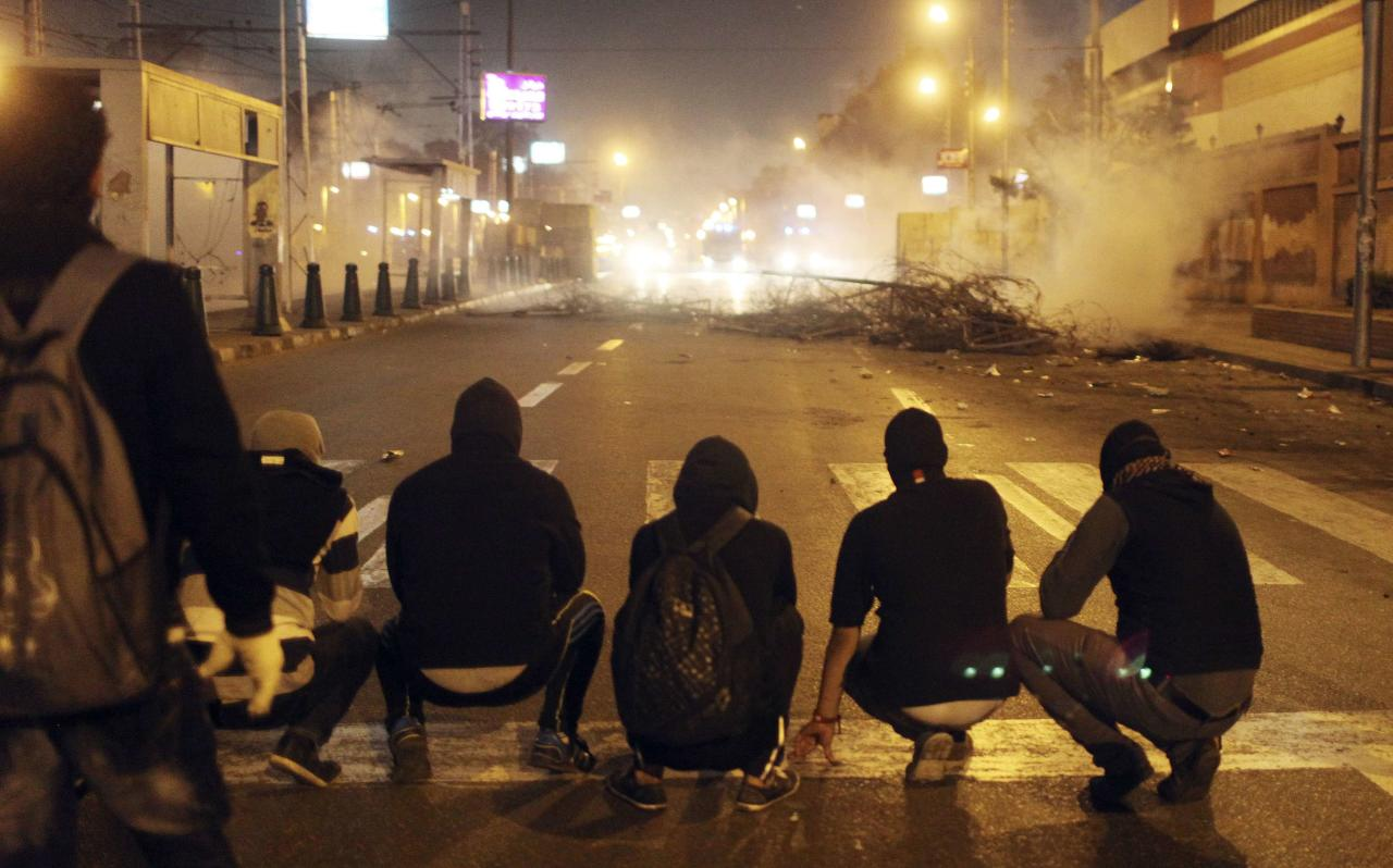 <p>Protesters sit in a line facing police vehicles after police fired tear gas (Reuters)</p>