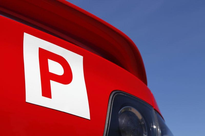 A red P-plate sits on the back of a car.