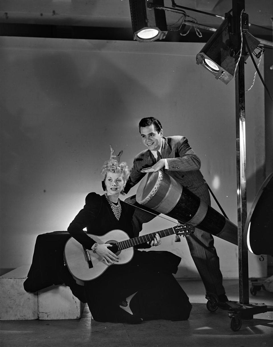 <p>Lucille and husband Desi Arnaz pose with instruments on the set of a magazine photoshoot. The couple eloped to Greenwich, Connecticut in 1940, shortly after meeting on the set of <em>Too Many Girls</em>. </p>