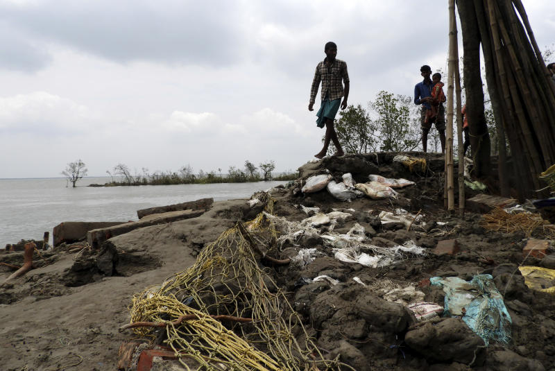 This May 22, 2020 photo shows villagers inspecting the damage after Cyclone Amphan struck Deulbari village, in South 24 Parganas district in the Sundarbans, West Bengal state, India. The cyclone that struck India and Bangladesh last month passed through the Sundarbans, devastating the islands that are home to one of the world's largest mangrove forests and is a UNESCO world heritage site. (Samrat Paul via AP)