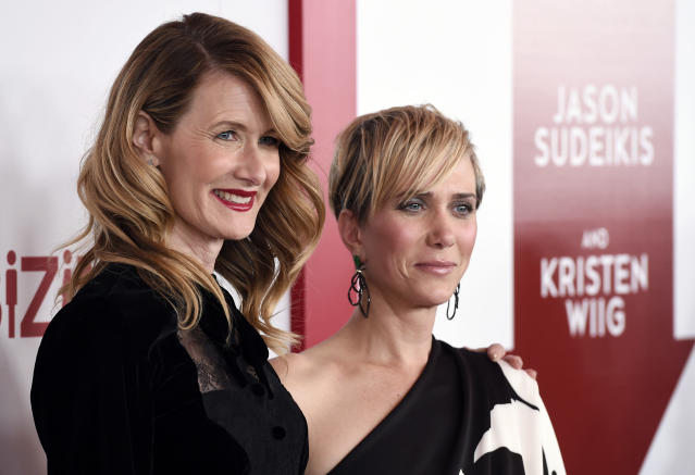 "Laura Dern, left, and Kristen Wiig, cast members in ""Downsizing,"" pose together at a special screening of the film at the Regency Village Theatre on Monday, Dec. 18, 2017, in Los Angeles. (Photo by Chris Pizzello/Invision/AP)"