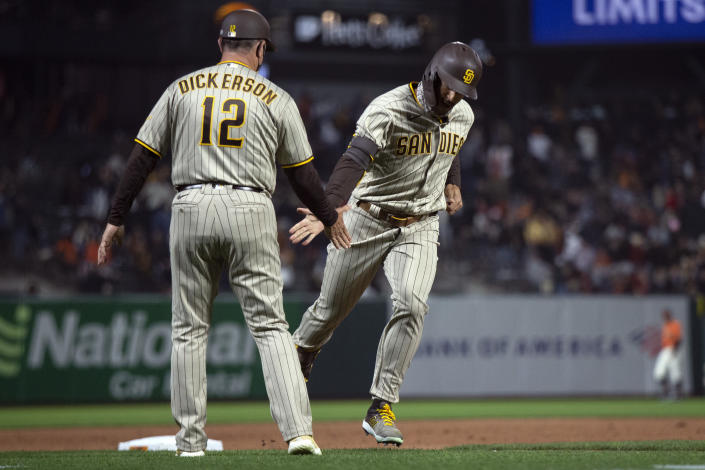 San Diego Padres' Trent Grisham, right, gets a congratulatory handshake from third base coach Bobby Dickerson (12) after hitting a two-run home run against the San Francisco Giants during the sixth inning of a baseball game, Friday, May 7, 2021, in San Francisco. (AP Photo/D. Ross Cameron)