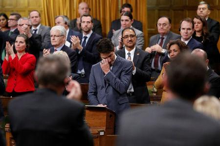 Canada's PM Trudeau wipes away tears while delivering an apology to members of the LGBT community on Parliament Hill in Ottawa