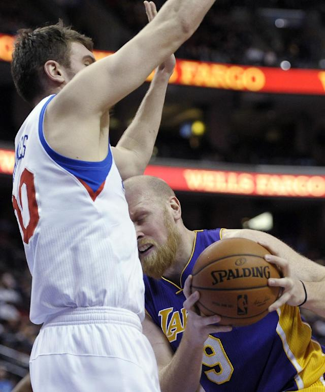 Los Angeles Lakers' Chris Kaman (9) drives to the basket as Philadelphia 76ers' Spencer Hawes (00) defends during the first half of an NBA basketball game on Friday, Feb. 7, 2014, in Philadelphia. (AP Photo/Michael Perez)
