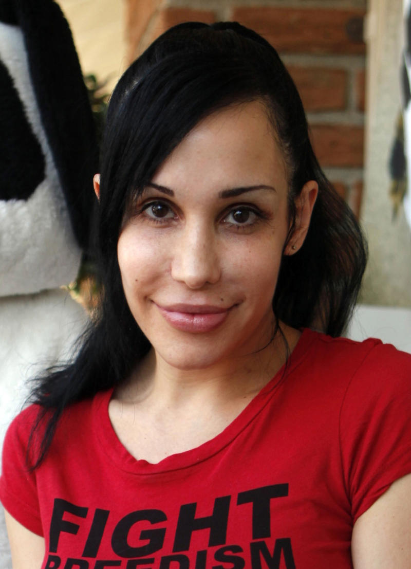 """FILE - In this May 19, 2010 file photo, """"Octomom"""" Nadya Suleman poses for photos outside her La Habra, Calif., home. Police and California child welfare officials who visited  Suleman's home after someone claimed that her 14 children were living in squalor say they did not find evidence that the children are in any danger.(AP Photo/Damian Dovarganes, File)"""