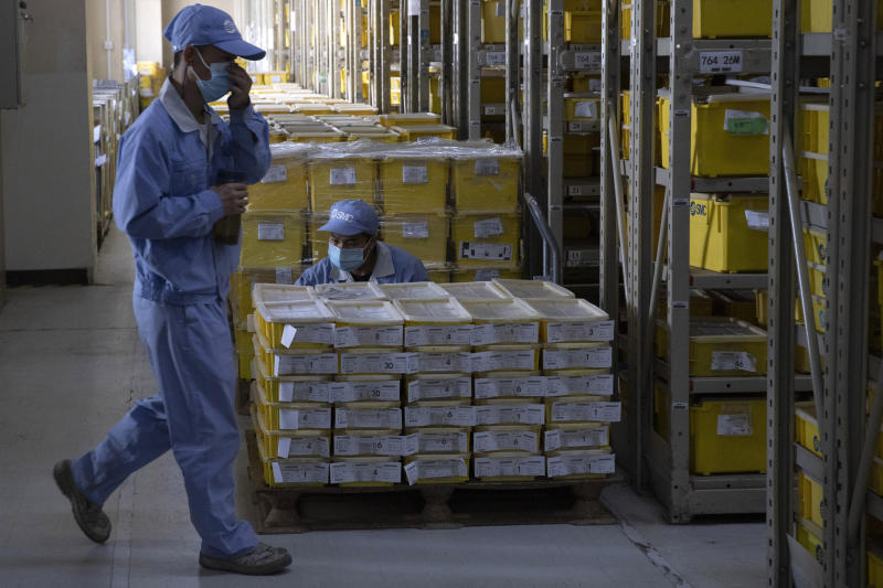 Worker examine inventory of parts produced at a factory of SMC, a Japanese pneumatic engineering company, in Beijing on Wednesday, May 13, 2020. Foreign invested enterprises in China are stepping up the resumption of business as the government strives to bring the country out of the economic slump caused by the epidemic of COVID-19. (AP Photo/Ng Han Guan)