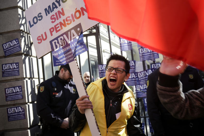 """A man protests holding a banner reading in Spanish """"The elder people without their pension"""" outside a BBVA bank building in Madrid, Spain, Friday, Feb. 15. 2019. Hundreds of Chinese have protested outside a Spanish bank's premises in Madrid, claiming they are being denied access to their accounts while the bank insists it is obeying money-laundering laws. (AP Photo/Andrea Comas)"""