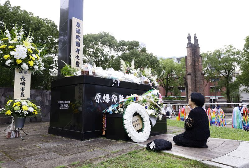 A woman prays for victims of the 1945 atomic bombing on a day commemorating the 75th anniversary of the bombing in Nagasaki, Japan