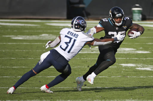 Jacksonville Jaguars running back James Robinson, right, gains yardage as he tires to get past Tennessee Titans safety Kevin Byard (31) during the second half of an NFL football game, Sunday, Dec. 13, 2020, in Jacksonville, Fla. (AP Photo/Stephen B. Morton)