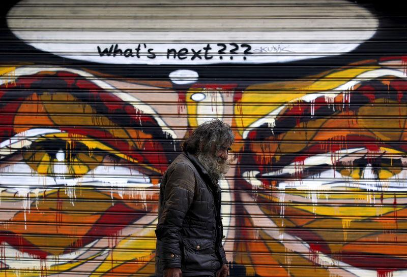 A man walks by a mural in Athens