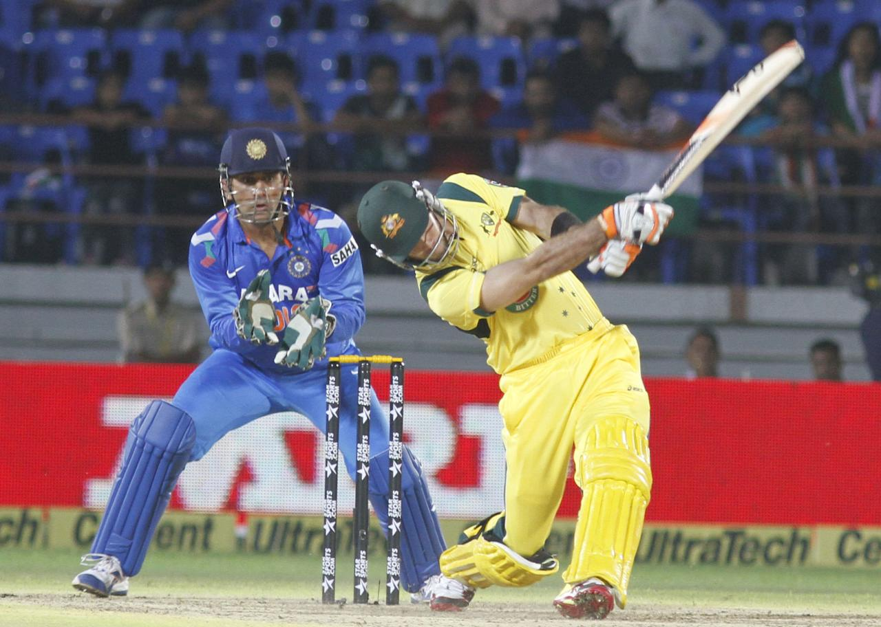 Australian batsman Glenn Mexwell plays a shot during the T20 match between India and Australia in Rajkot on 10 October 2013. (Photo: IANS)