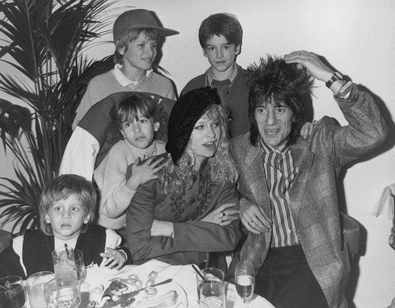 Rolling Stones guitarist Ron Wood with his wife Jo and their children, Jamie, Jesse, Tyrone and Leah, 19th February 1988. The family are dining out on the opening night of 51/51, a new London restaurant, where Wood is exhibiting some of his paintings. (Photo by Dave Hogan/Hulton Archive/Getty Images)