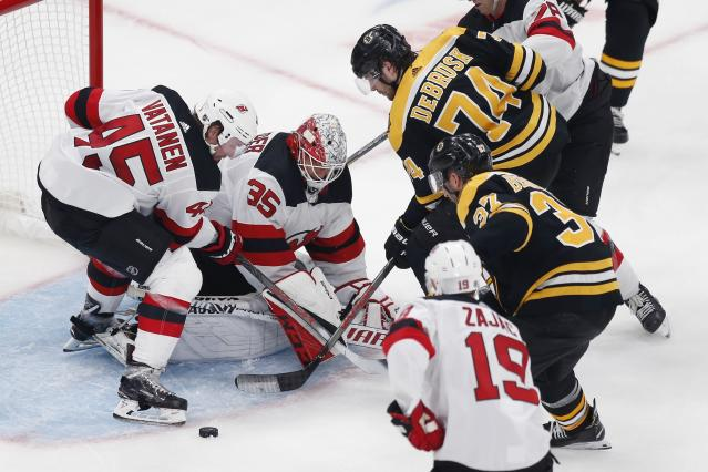New Jersey Devils' Cory Schneider (35) and Sami Vatanen (45) struggle to gain control of the puck as Boston Bruins' Patrice Bergeron (37) comes in to score during the second period of an NHL hockey game in Boston, Saturday, Oct. 12, 2019. (AP Photo/Michael Dwyer)