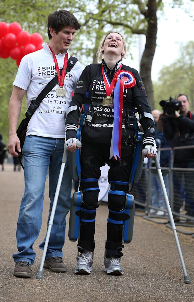 LONDON, ENGLAND - MAY 08:  Claire Lomas stands with her husband Dan Spincer (L) after crossing the finishing line of the Virgin London Marathon on May 8, 2012 in London, England. Ms Lomas, who is paralysed from the waist down after a riding accident in 2007, has taken 16 days to complete the 26.2 mile route. Starting out with 36,000 other runners she has averaged 2 miles a day with the help of a bionic ReWalk suit.  (Photo by Peter Macdiarmid/Getty Images)