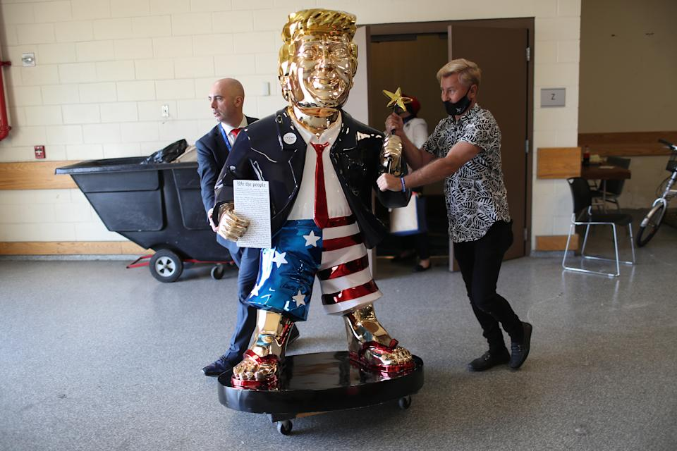 ORLANDO, FLORIDA - FEBRUARY 27: Matt Braynard (L) helps artist Tommy Zegan (R) wheel his statue of former President Donald Trump to a van during the Conservative Political Action Conference on February 27, 2021 in Orlando, Florida. Begun in 1974, CPAC brings together conservative organizations, activists, and world leaders to discuss issues important to them.  (Photo by Joe Raedle/Getty Images)