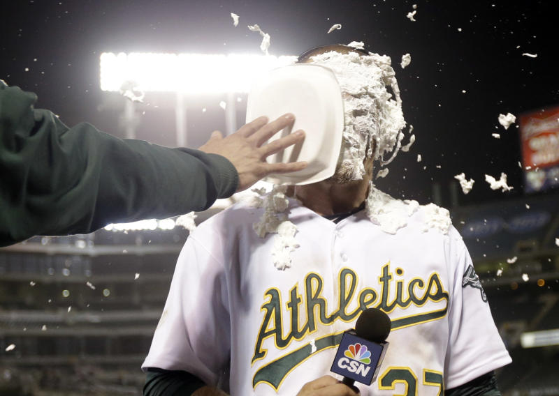 Oakland Athletics' Brandon Moss gets a shaving cream pie to the face as he conducts an interview after his game winning two-run home run against the Los Angeles Angels during a baseball game on Tuesday, April 30, 2013 in Oakland. Calif. Oakland won 10-8 in 19 innings. (AP Photo/Marcio Jose Sanchez)