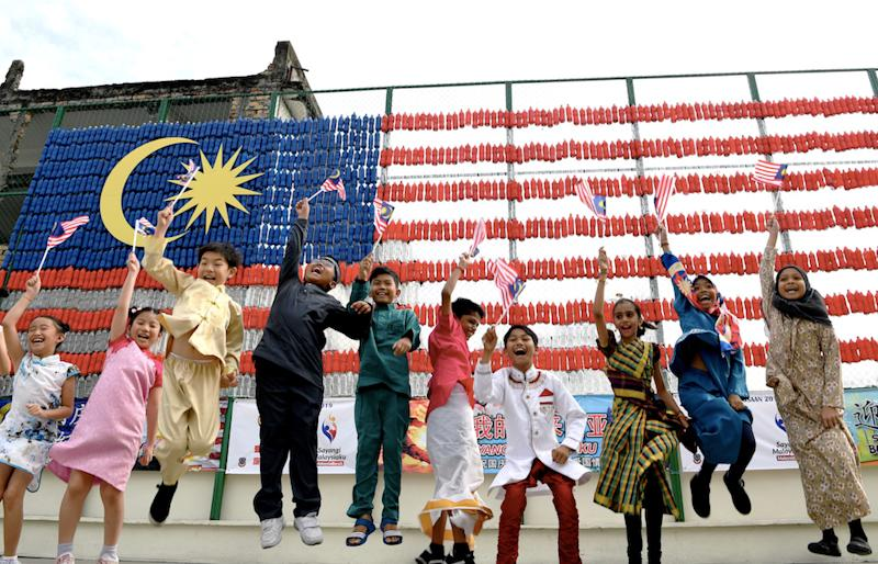 Penang students jump for joy in front of the national flag made out of recycled mineral water bottles. — Bernama pic